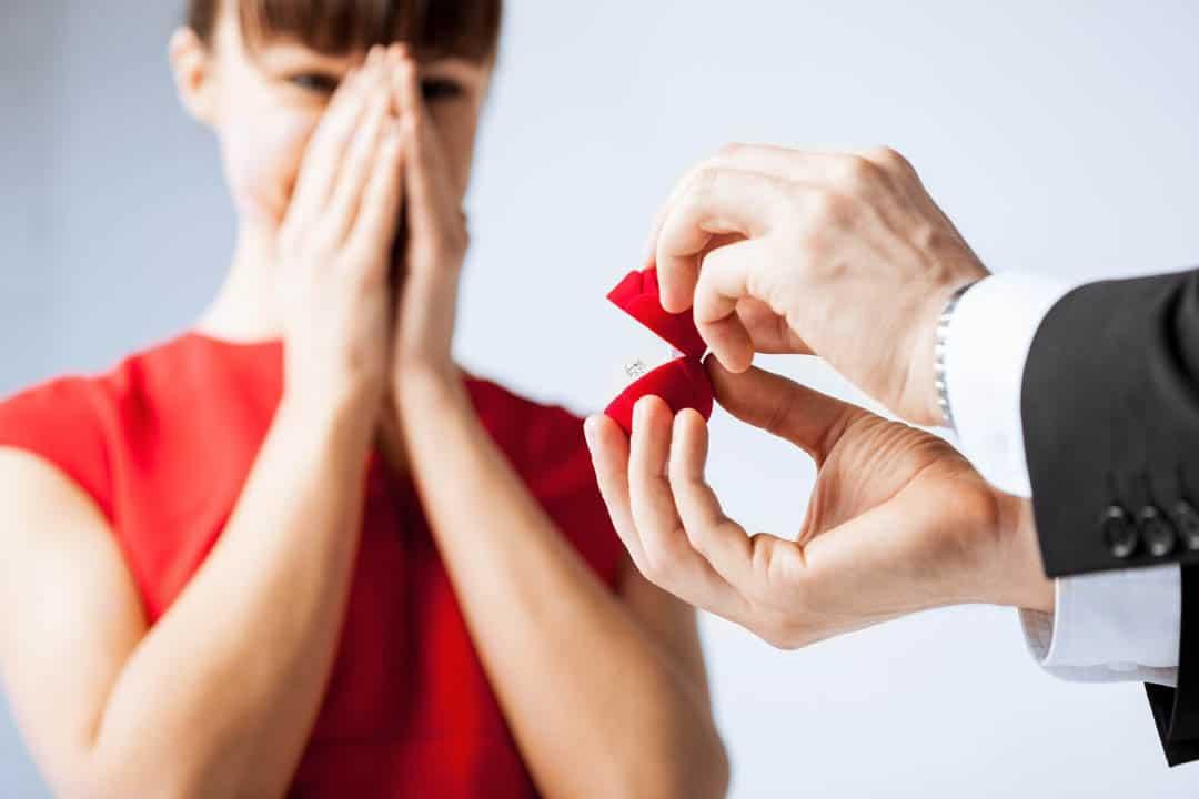 Männerhände öffnen eine Ringschachtel und zeigen den Ring der überraschten, angehenden Braut