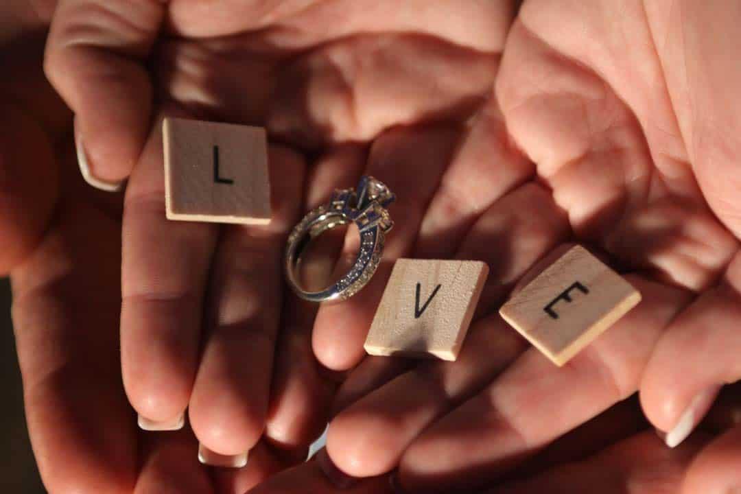 Hände halten einen Ring und die Buchstaben L, V und O was zusammen das Wort LOVE ergibt