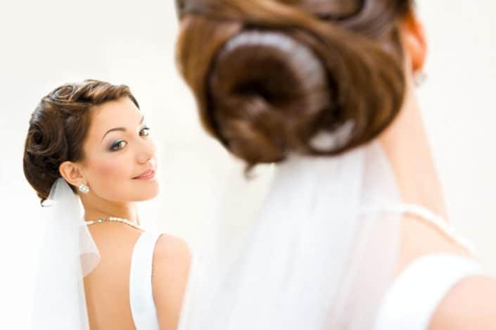 Braut mit Hochsteckfrisur betrachtet sich im Spiegel