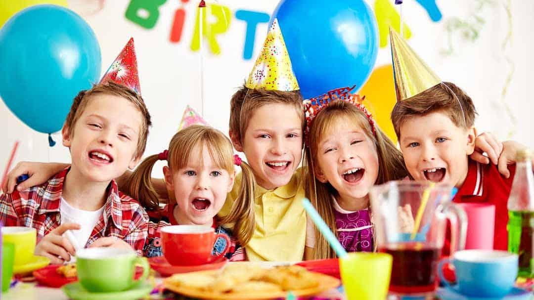 Fünf Kinder mit Partyhüten feiern einen Geburtstag