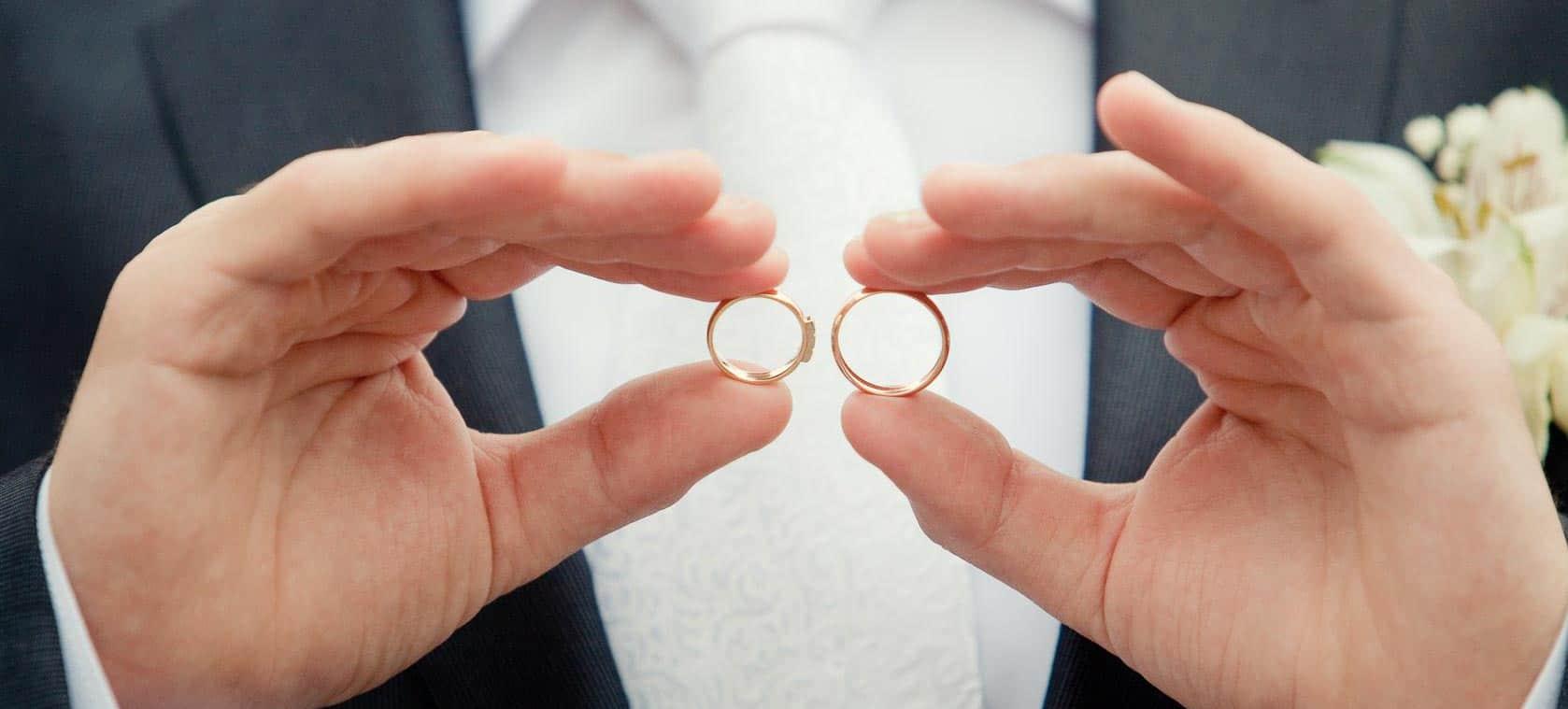 Mann hält zwei Eheringe