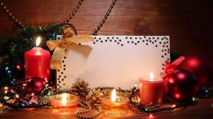 Weihnachtsdekoration mit Briefumschlag, Kerzen und Christbaumschmuck