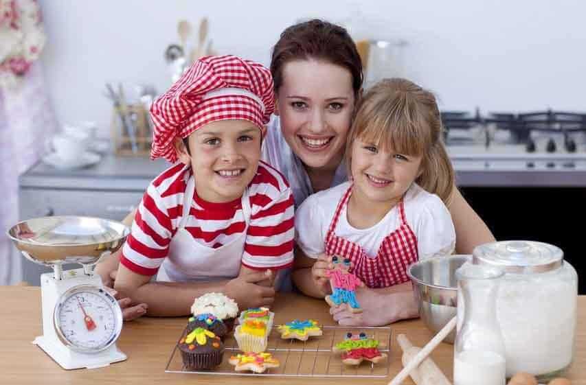 Mutter und zwei Kinder mit Backutensilien in der Küche lächeln in die Kamera