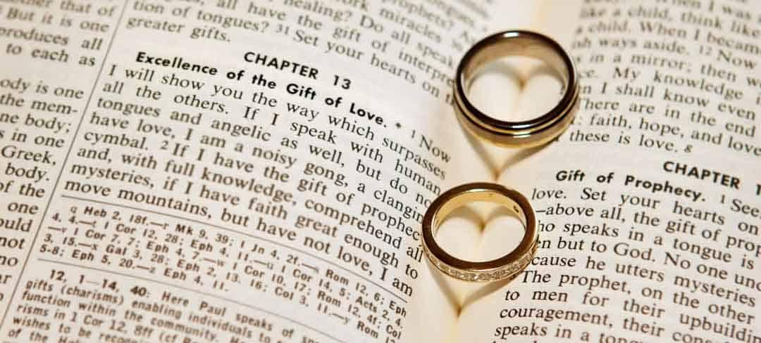 Zwei Eheringe liegen in aufgeschlagener Bibel