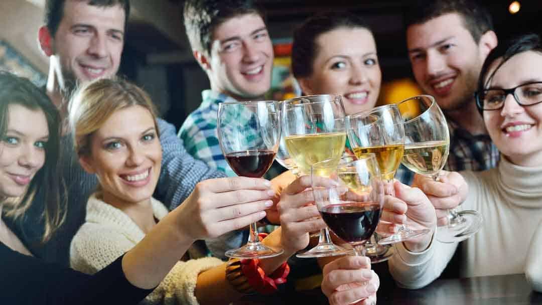 Eine Gruppe Menschen stösst mit Weingläsern an