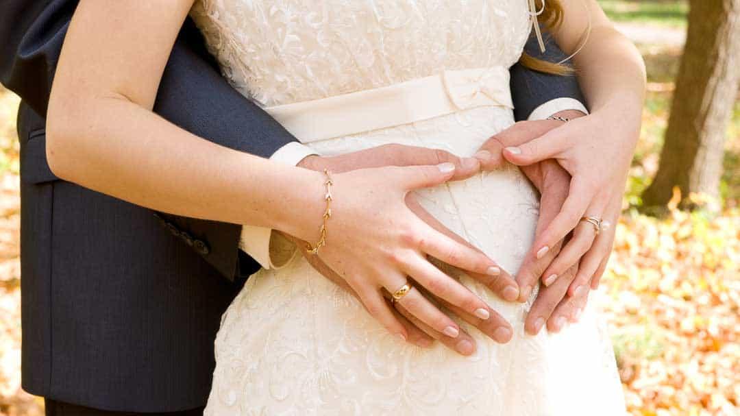 Hände eines Brautpaares auf dem Bauch der schwangeren Braut